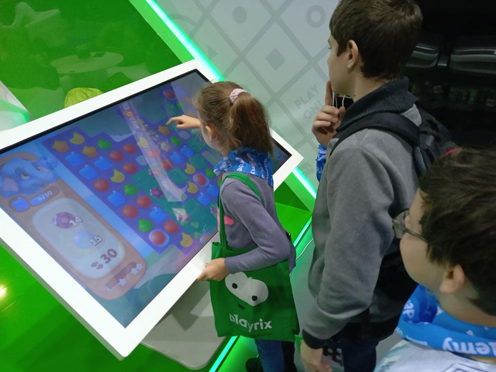 Ещё один большой экран, но с другой игрой на стенде Playrix